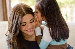 young-girl-whispers-to-mother
